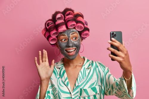 Happy positive woman applies clay mask on face to rejuvenate skin applies hair rollers waves hello at camera holds cellular in front dressed in domestic clothes isolated over pink background