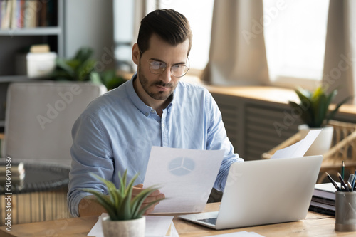 Concentrated young businessman ceo manager in eyewear looking at marketing research report, analyzing statistics data in charts, developing growth strategy, working on computer alone in modern office.