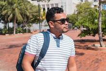 Casual Young Man With Sunglasses Walking Down The Street With His Backpack Facing Away From Him.