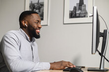 Cheerful Multiracial Guy In Smart Casual Shirt Is Using A PC For Work. Young African Businessman Is Typing On Keyboard, And Looking On Computer Screen At Home Office