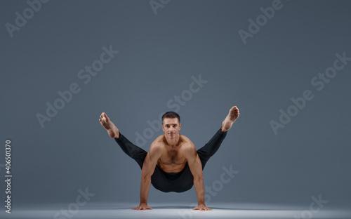 Fototapeta premium Male yoga doing stretching exercise in studio