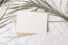 Summer Tropical Stationery Still Life Scene. Dry Date Palm Leaf On White Table Cloth In Sunlight. Blank Greeting Card, Invitation Mockup With Craft Paper Envelope. Long Shadows. Vacation Flat Lay, Top