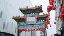 London's Beautiful Chinatown Entrance Gate With Chinese Lanterns Swaying In The Wind On An Overcast Day In Slow Motion.