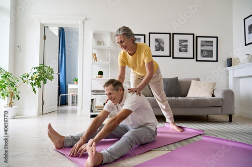Obraz Fit active retired middle aged wife helping senior husband doing stretching exercise at home. Happy healthy older senior 60s couple enjoying fitness sport training workout together in apartment. - fototapety do salonu
