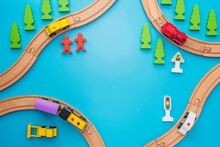 Baby Kid Toys Background. Toy Train And Wooden Rails On Blue Background. Top View. Children Toys, A Trains And Cars Traveling On Wooden Roads With Trees, People And Roadsigns On Blue Background