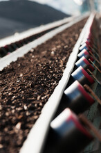 Vertical Shot Of Coal Being Transported By A Rubber Conveyor Belt With A Blurry Background