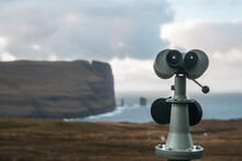 Closeup Of A Tower Viewer On The Ground Surrounded By Cliffs And The Sea Under A Cloudy Sky