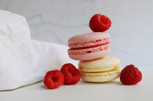 Photo Of Pink And White Macaroon With Raspberries With Crumpled Linen Cloth On The Edge Of The Table