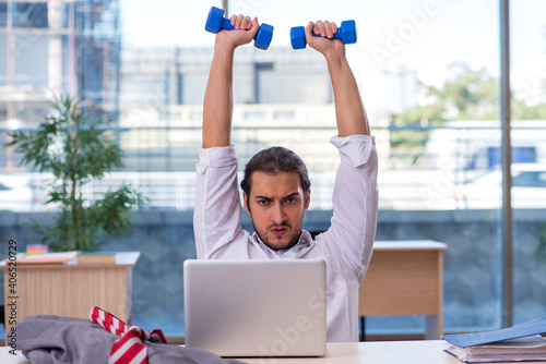 Obraz Young male employee doing sport exercises in the office - fototapety do salonu