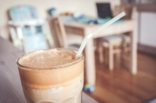 Closeup Shot Of A Glass Of Iced Coffee On A Table With Drinking Straw And A Blurred Background
