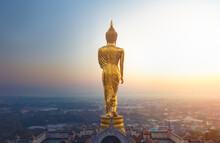 Golden Buddha Standing Statue On A Mountain Wat Phra That Khao Noi At Sun Rises, Nan Province, Thailand