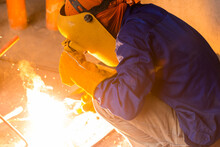 A Welder In Full Protective Gear Crouches Down And Welds Some Makeshift Tools. Hot Sparks Fly From The Welding Point.