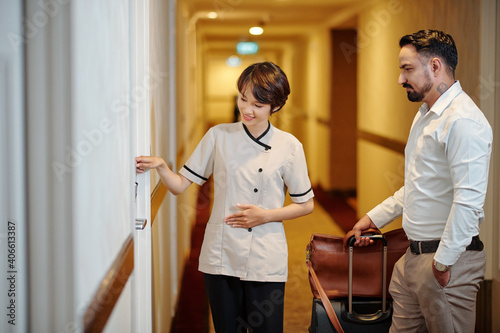 Young pretty hotel manager in uniform explaining guest how to open room door wit Fototapet