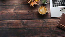 Top View Of Hipster Vintage Workspace With Laptop, Stationery Notebooks And A Cup Of Coffee On Wooden Table. Copy Space For Advertise Text.
