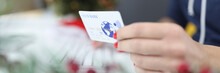 Female Hand Holds Bank Credit Plastic Card. New Year Sales In Online Stores Concept