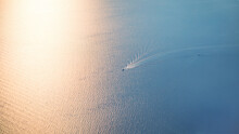 Sea Surface Aerial View. Glowing Sea At Sunset Or Sunrise With Waves Pattern