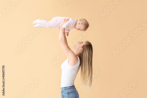 Fotografija Happy mother with cute little baby on color background