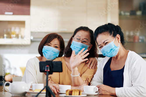 Fotografering Group of senior Asian women in medical masks recording video for subscribers or