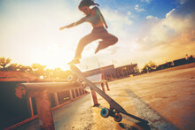 Young Woman Practising Skateboarding At Skate Park. Women Try To Playing Skateboard Jumping At The Roll Bar With Sunset Background.