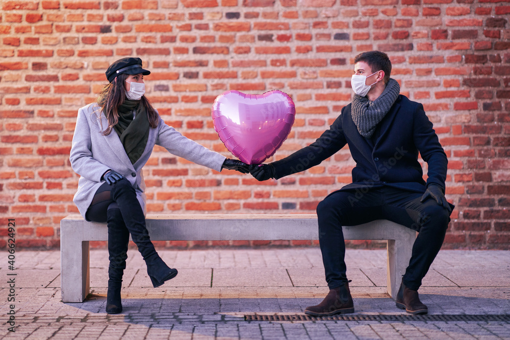 Fototapeta Happy couple celebrating Valentines Day in masks during covid-19 pandemic