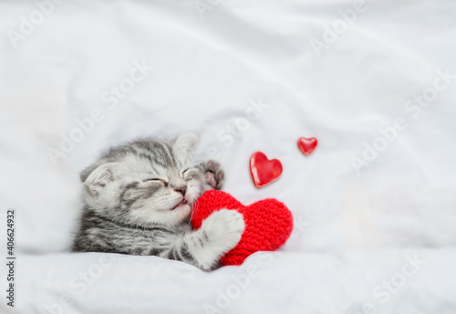 Happy kitten holds red heart and sleeps on a white bed. Valentines day concept. Top down view. Empty space for text