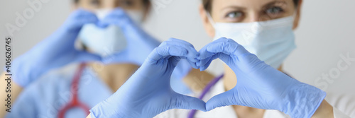 Slika na platnu Two doctor in medical masks and rubber gloves showing heart with their hands