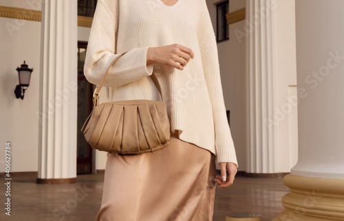 Obraz Closeup beige leather bag in hand of fashion woman in silk skirt. Elegant fall and spring outfit. - fototapety do salonu