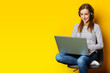Young woman in headphones sitting on chair and holding laptop on isolated yellow background