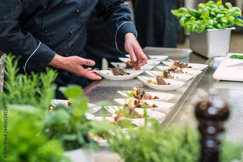 Photographie Catering Koch bereitet kleine Teller mit Spießen vor