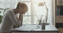 Exhausted Woman With Headache Working In Her Office
