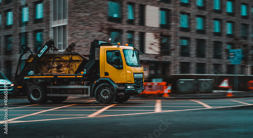 Fotografiet Panning shot of a yellow dumpster truck taking a turn in an english city of Cambridge