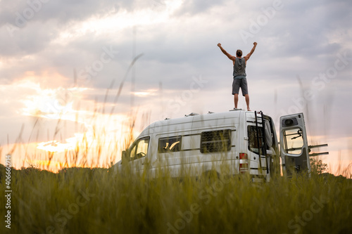 Fotografering Man with raised arms on top of his camper van