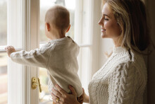 Mother And Her Little Baby Son Wearing Warm Sweaters Looking At The Window