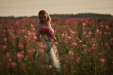 Young Beautiful Girl With A Bouquet Of Flowers In Her Hands At Sunset.