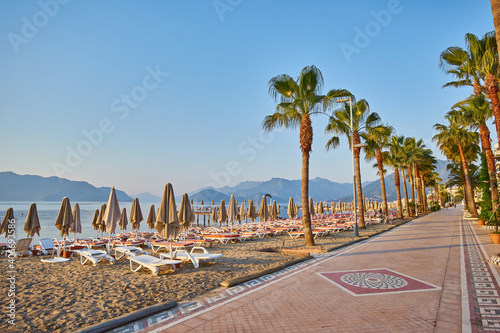 Obraz na plátně sandy beach without people and with sun loungers, folded umbrellas, palm trees,