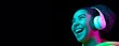 Laughting, flyer. African-american woman isolated on dark background in multicolored neon. Listening to music with headphones. Concept of human emotions, facial expression, sales, ad, fashion.