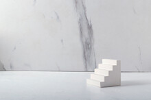 Bright Stone Stairs On The White Desk Against Marble Wall.Empty Space