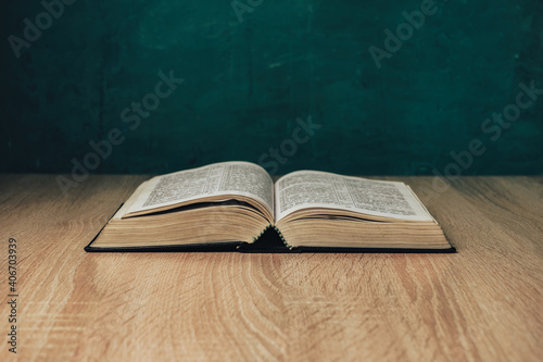 Open holy bible on a  wooden table. Beautiful green wall background.
