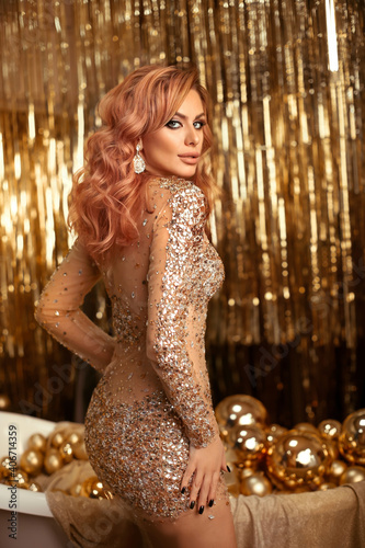 Christmas Woman portrait over gold xmas gifts and balls in bathtub. Beauty fashion model girl with make up, wavy hair and jewellery, posing in golden gems dress over bright bokeh background.