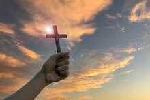 Silhouette Hand Holding Wood Cross Against Sunrise Background, Open Palm Up Worship, Pray For Blessings From God. Christian Religion, Crucifix And Faith Concept