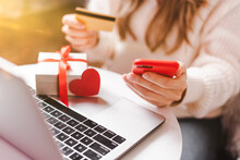 Close Up Of Woman Hands With Mobile Phone, Credit Card, Gifts And Laptop. Online Shopping At Christmas, Valentine Day Or Birthday Holidays. Freelance Girl Woking From Home Office