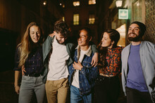 Group Of Young Adult Friends Walking In The Street Together At Night