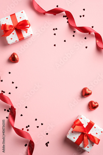 Valentines day flat lay composition with red ribbon, gifts, confetti on pink background. Suitable for vertical banner, flyer, brochure, stories on social media
