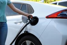 Woman Inserting Plug Into Electric Car Socket At Charging Station, Closeup