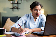 Young Business Woman Writing Down Notes By Looking Laptop - Concept Of Employee Or Student Online Training Class At Home.