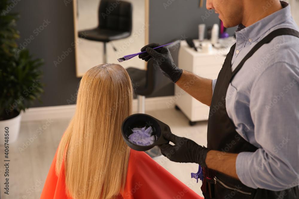 Fototapeta Professional hairdresser dying hair in beauty salon, closeup