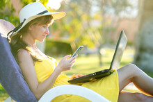 Girl Student In Yellow Summer Dress Resting On Green Lawn In Summer Park Studying On Computer Laptop Texting On Mobile Cell Phone. Doing Business And Learning During Quarantine Concept.