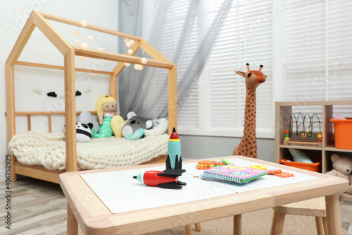 Cute child's room interior with toys and wooden furniture