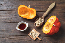 Pumpkin Seed Oil In A White Bowl, Fresh Autumn Pumkins And Pumkin Seeds In Wooden Spoons And On A Dark Wooden Table, Top View