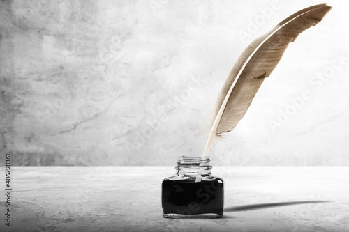 Fototapeta Feather quill pen and glass inkwell on desk obraz